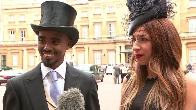 London Buckingham Palace EXT Tania Farah interview SOT Sir Mo Farah posing with knighthood medal
