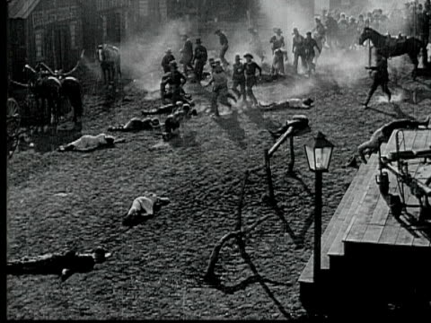 1916 B/W MONTAGE MS WS HA Mob running away from burning church, through street lined with dead and wounded people, two women carrying wounded man away from fire, 1880s / Santa Monica, California, USA