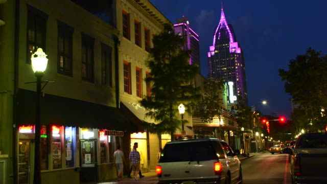 Mobile Alabama downtown traffic on Dauphin Street at twilight with Trustmark Skyscraper in the background at night