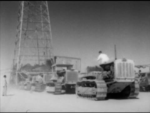 Mobile oil derrick being pulled by tractors over sand Teamwork dangerous work petroleum gasoline remote location nonsustainable fossil fuel Global...