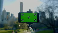 Mobile phone on selfie stick with green screen Central Park