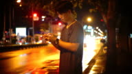 Mobile phone use, A men using smart phone on the street at night.