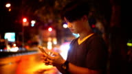 SEA: Mobile phone use, A men using smart phone on the street at night.