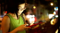 SEA: Mobile phone use, Asian woman using on digital tablet computer touchscreen iPad while sitting in the street at night.