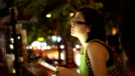 SEA: Mobile phone use, Asian woman using on mobile phone while sitting in the street at night.