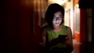 SEA: Mobile phone use, Asian women using smart phone at night in the city.