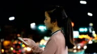 SEA: Mobile phone use, Attractive Asian Woman using Mobile Phone During Walk on Streets of Night Town