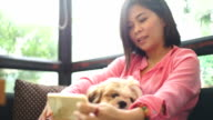 SEA: Mobile phone use, Relaxed woman using smart phone with her dog in the cafe.