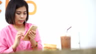 SEA: Mobile phone use, Women taking photo of breakfast with iced chocolate on wooden table with smartphone.