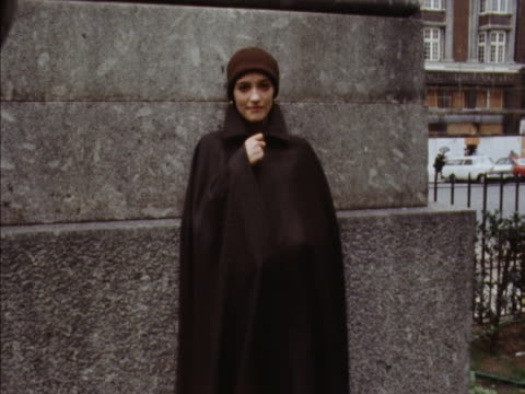 A model poses wearing a full length cape hat blouse and trousers from Yves St Laurent's new collection 1969