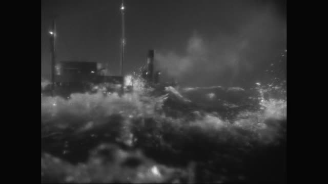 WS Model steam ship sailing in rough, stormy sea with high waves at night / United States