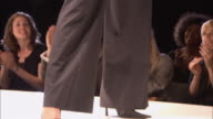 WS Model wearing a suit with a large belt around the waist posing on catwalk in front of audience at fashion show/ London, England