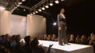 WS Model wearing suit with a large belt posing on catwalk at fashion show/ London, England