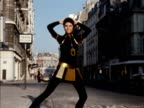 A model wears a black cat suit with a gold plastic mini skirt and chain accessories 1970