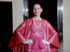 A model wears a bright pink embroidered dress with a matching silk coat designed by Norman Hartnell