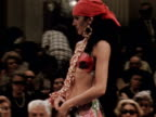 A model wears a gypsy inspired bikini and skirt desgined by Ken Short at a fashion show in Florence