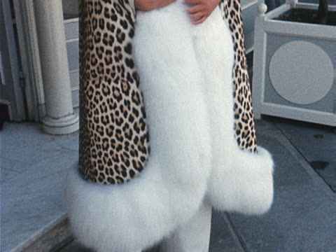 A model wears a leopard print coat trimmed with white fox fur
