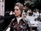 A model wears a patterned dress with a matching turban