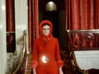A model wears a red suede catsuit and matching hat at a fashion show