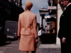 A model wears a salmon pink dress and jacket designed by Clive on a London street 1968
