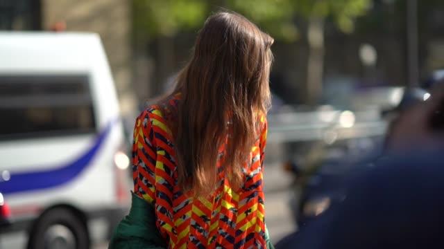 A model wears an orange shirt a green jacket outside the Dries Van Noten show during Paris Fashion Week Womenswear Spring/Summer 2018 on September 27...