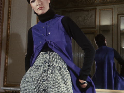 A model wears 'knickair' trousers underneath a sleeveless coat