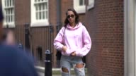 A model wears sunglasses a pink hoodie ripped jeans black shoes outside Simone Rocha during London Fashion Week September 2017 on September 16 2017...