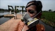 Modelos desfilaron este martes con mascaras de gas y botas de goma sobre una pasarela instalada en un arrozal en Indonesia para denunciar el papel de...