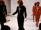Models attempt formation dancing whilst wearing red and black shiny jackets and Bermuda shorts berets and skirts at a Courreges fashion show in Paris...
