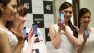 Models display SoftBank Corp's new smartphones during a product launch in Tokyo A model displays a SoftBank Corp Disney Mobile branded DM015K...
