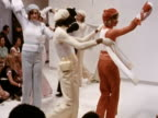Models moving in conga style wear slacks knitted jumpers and berets and wave scarves at a Courreges fashion show in Paris 1972