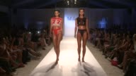 Models walk the runway during Minimale Animale MercedesBenz Fashion Week Swim 2014 at Oasis at the Raleigh Hotel on July 22 2013 in Miami Florida