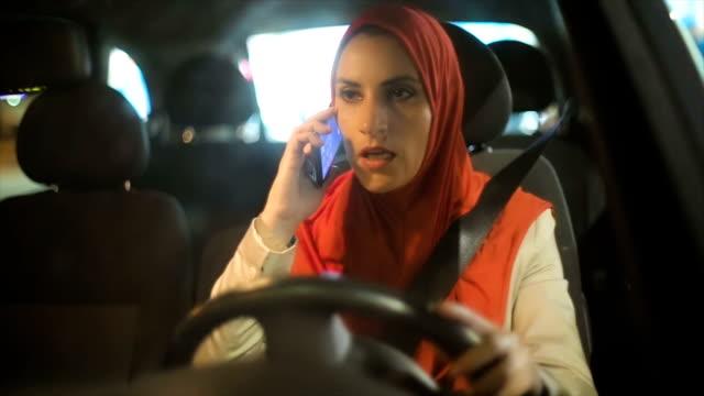 Moderne arabische Frau mit Handy im Auto