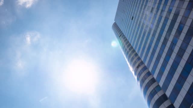 modern blue building with glass wall  in blue sky.timelapse