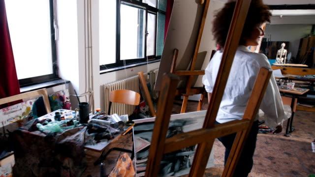 Modern funny woman artist enters in art studio