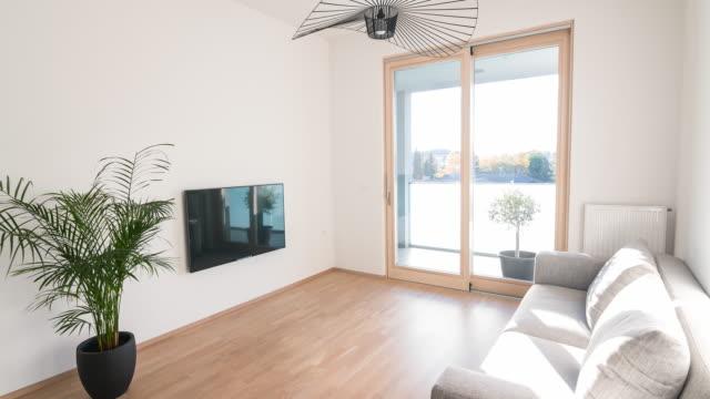 Modernt vardagsrum i en öppen planlösning lägenhet med minimalistisk inredning