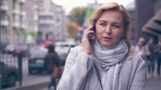 Moderne volwassen vrouw praten over de telefoon terwijl het lopen op straat