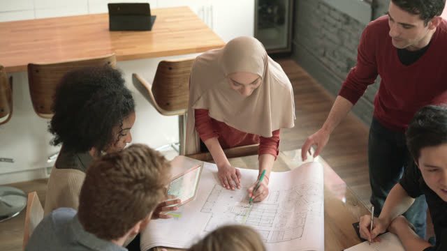 Modern Muslim woman wearing hijab lead the business meeting with multi-ethnic group of people. Explaining the drawing. Top view overhead.