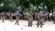 Mogadishu EXT Various of armed Al Shabaab militants in streets Armed men sitting on back of moving truck Women chanting Various of Al Shabaab...