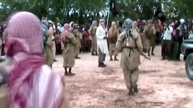 Various of armed Al Shabaab militants in streets and waving to crowds at parade