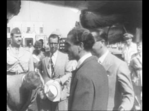 Mohammad Reza Shah Pahlavi deplanes in Iran walks down airstairs greets cleric on tarmac / Shah walks with man on tarmac / montage small crowd on...