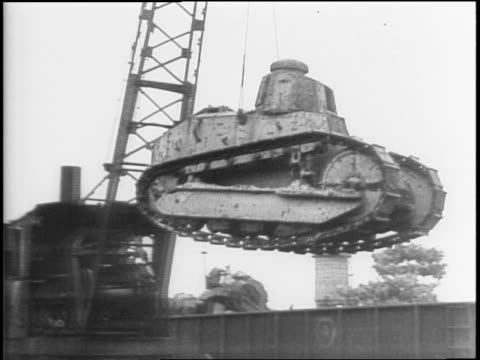Molten steel being poured and shaped / montage of WWI tank being moved onto scrap heap by crane at junkyard / pile of artillery shells / various...