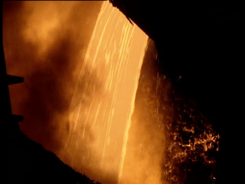 Molten steel poured into roaring fires of furnace