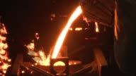 Molten steel pours from a bucket into a metal cylinder in a steel factory. Available in HD.