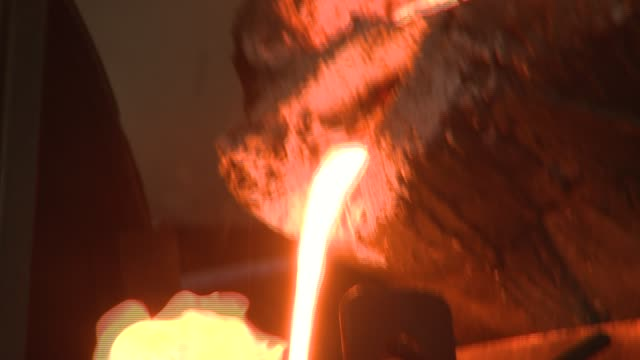Molten steel pours into a metal cylinder in a steel factory. Available in HD.