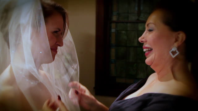 Mom adjust bride's veil and gives her a hug
