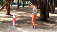 Mom and baby dancing in park