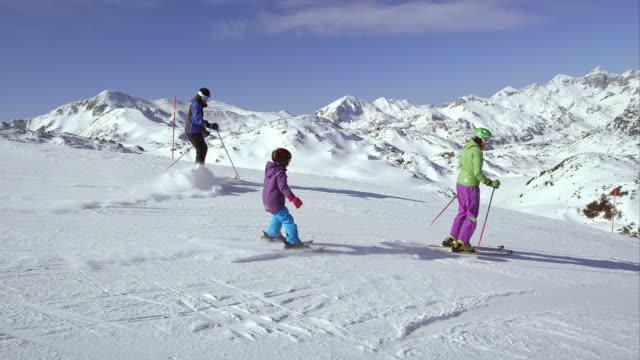 TS pappa en mamma onderwijzen hun dochter skiën