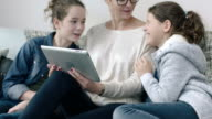 Mom and daughters looking at digital tablet