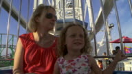 A mom and her daughter ride the Ferris Wheel together and look around them.